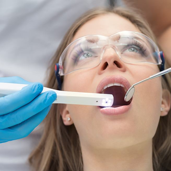Dentist using intraoral camera to capture images of patient's smile